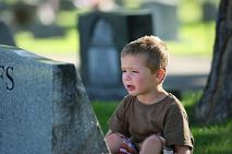 child crying in front of tombstone